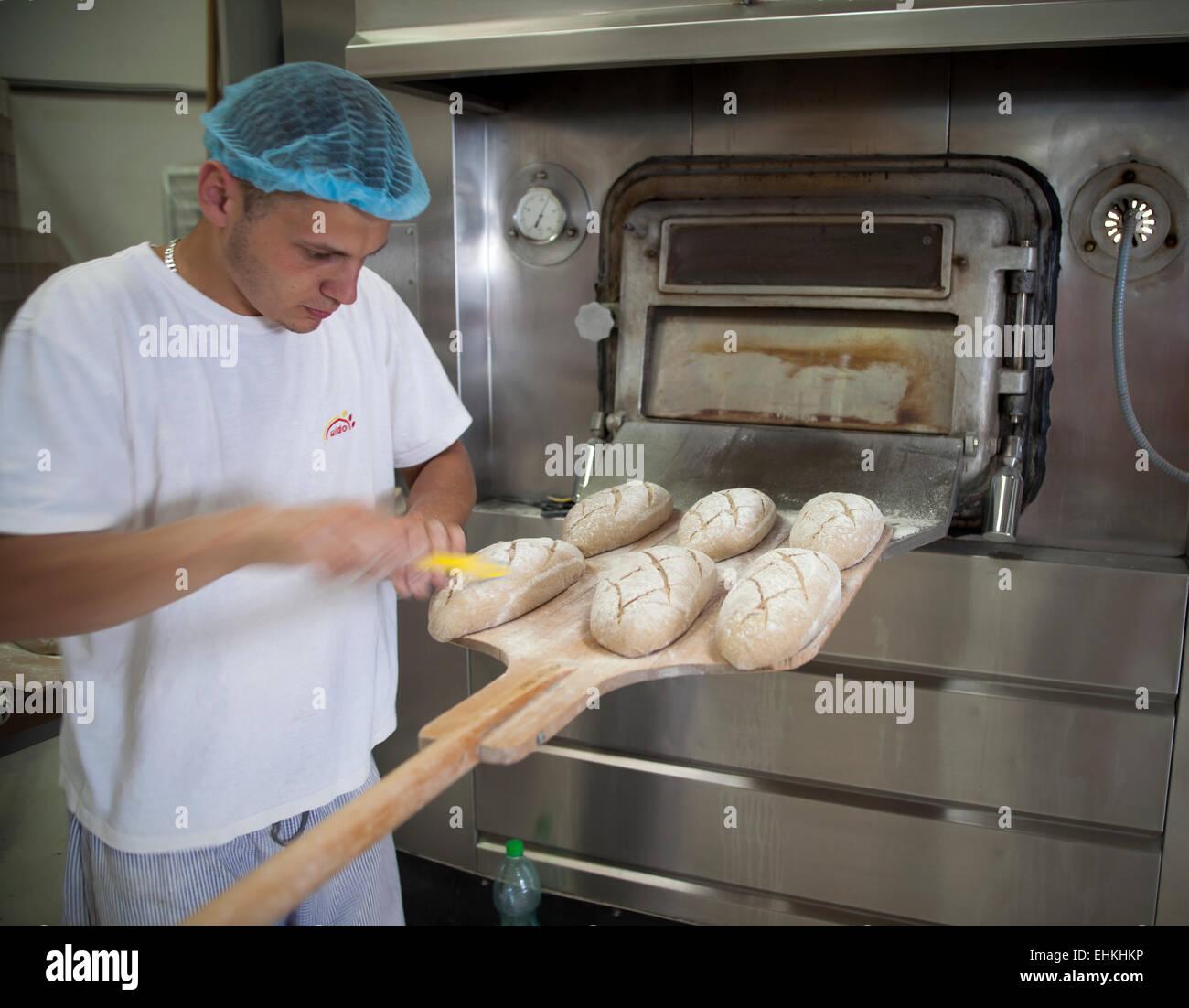 Baker vorbereiten Brote auf Paddel vor dem Einlegen in den Ofen Stockbild