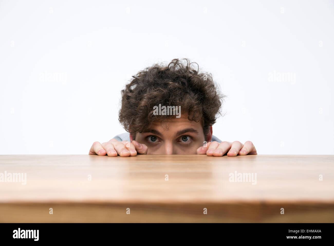 Junger Mann mit lockigem Haar spähen hinter dem Schreibtisch Stockbild
