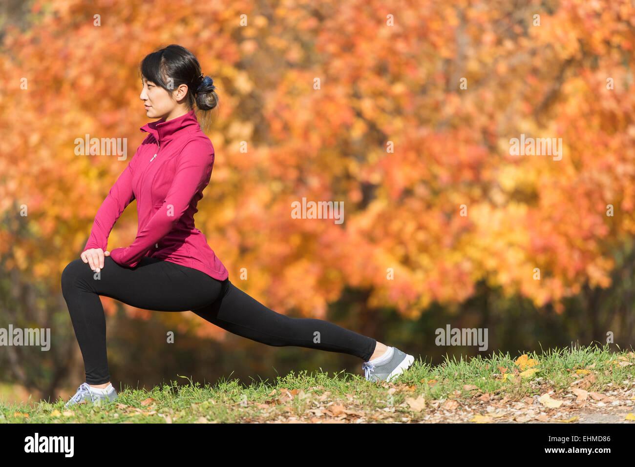 Asiatische Läufer Strecken im park Stockfoto