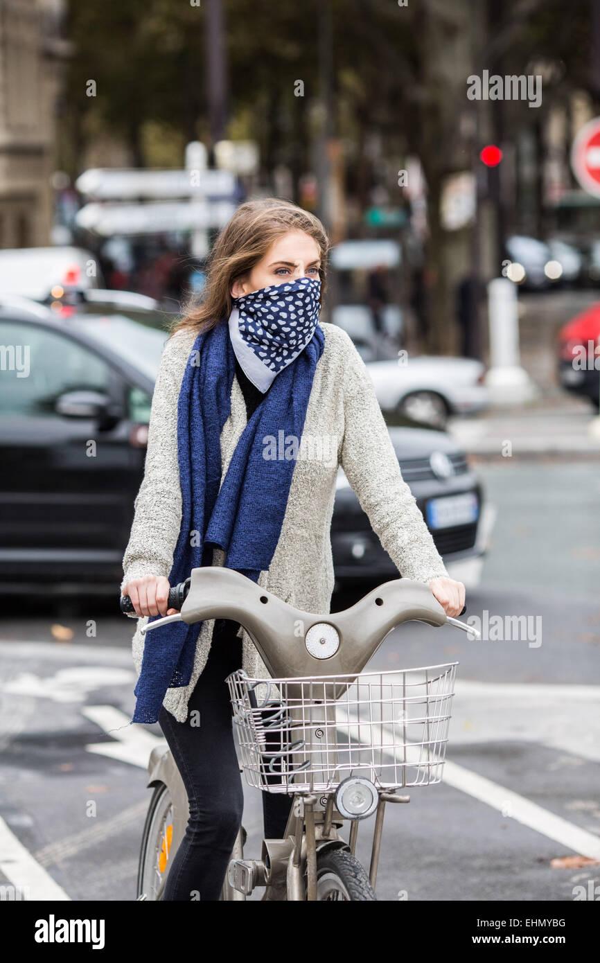 Frau reitet ein Fahrrad in einem städtischen Umfeld. Stockbild