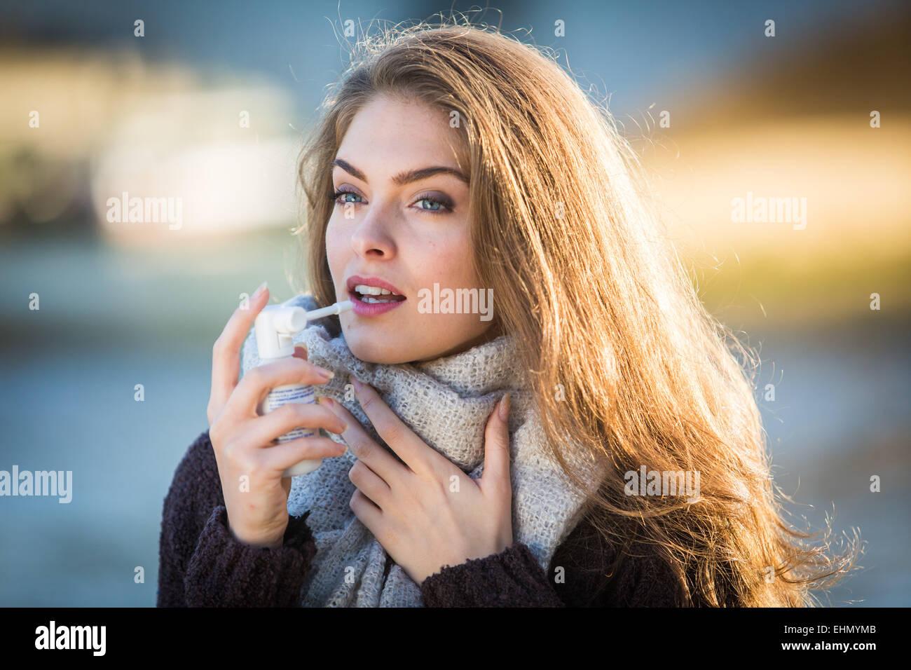 Frau mit Collutory-Spray für Sorethroat. Stockbild