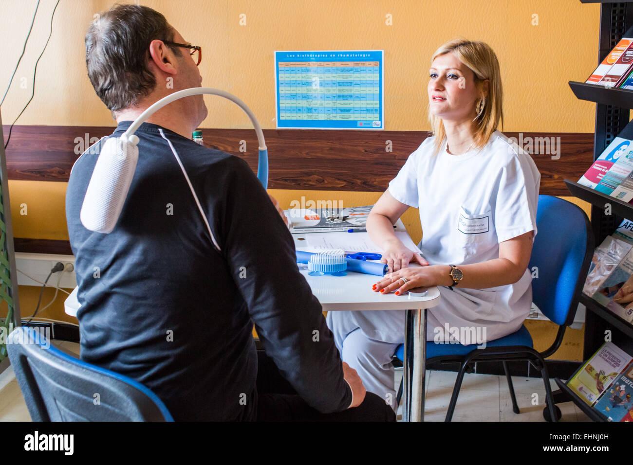 Funktionelle Beurteilung und Beratung zu technischen Hilfsmitteln durch eine Ergotherapeutin mit einem Patienten Stockbild