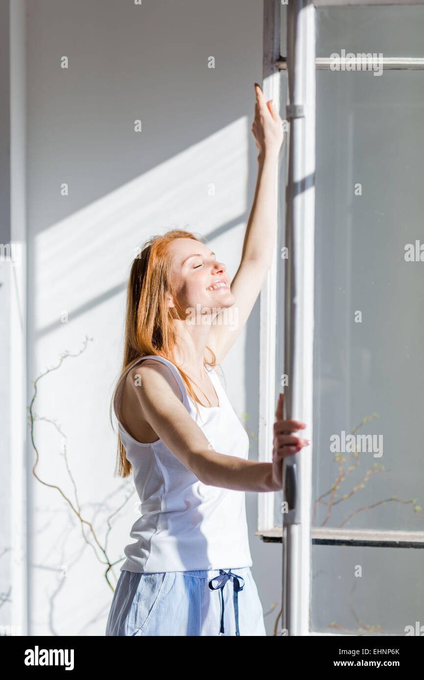 Frau zu öffnendes Fenster. Stockbild