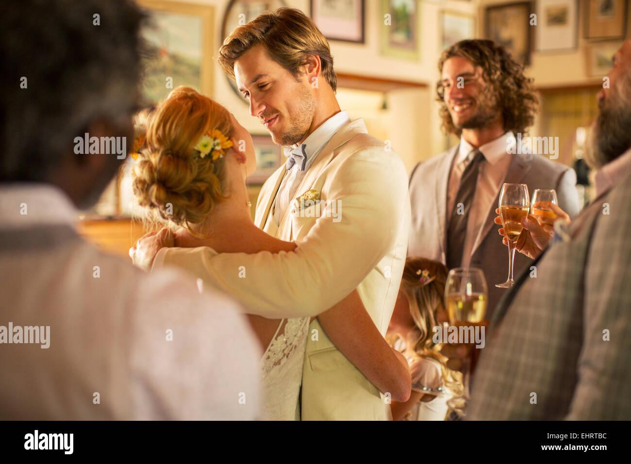 Bräutigam umarmen Braut während der Hochzeitsfeier im Wohnraum Stockbild