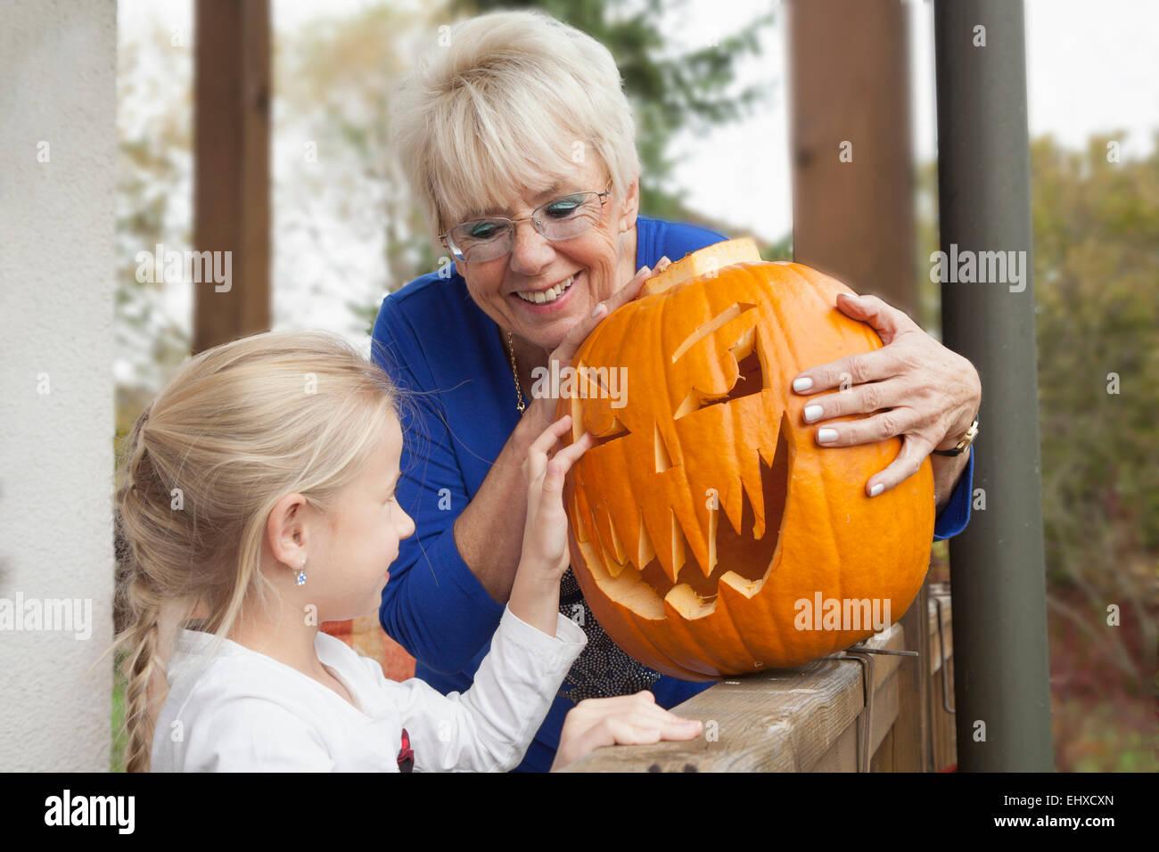 Ältere Frau, die Halloween-Kürbis zu ihrer Enkelin, Bayern, Deutschland Stockbild