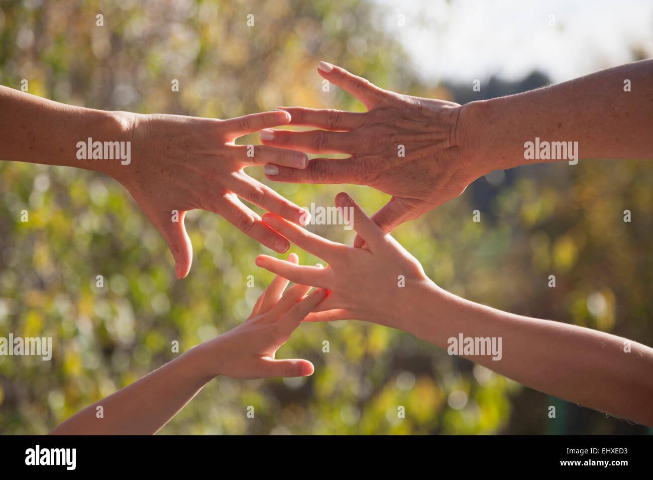 Nahaufnahme von Familienhand gemeinsam gegen Sonnenlicht, Bayern, Deutschland Stockbild