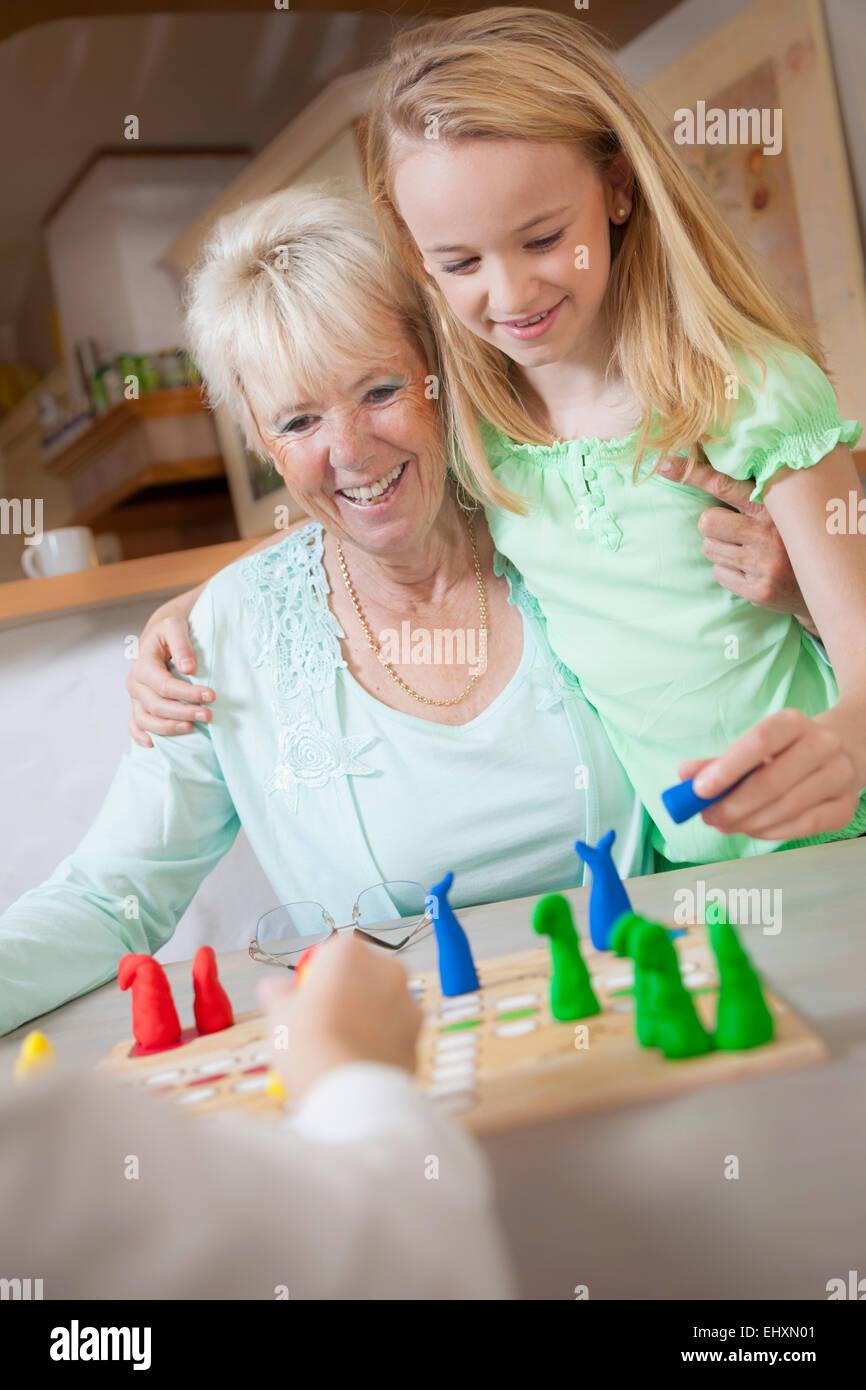 Mädchen spielen Brettspiel mit ihrer Großmutter, Bayern, Deutschland Stockbild