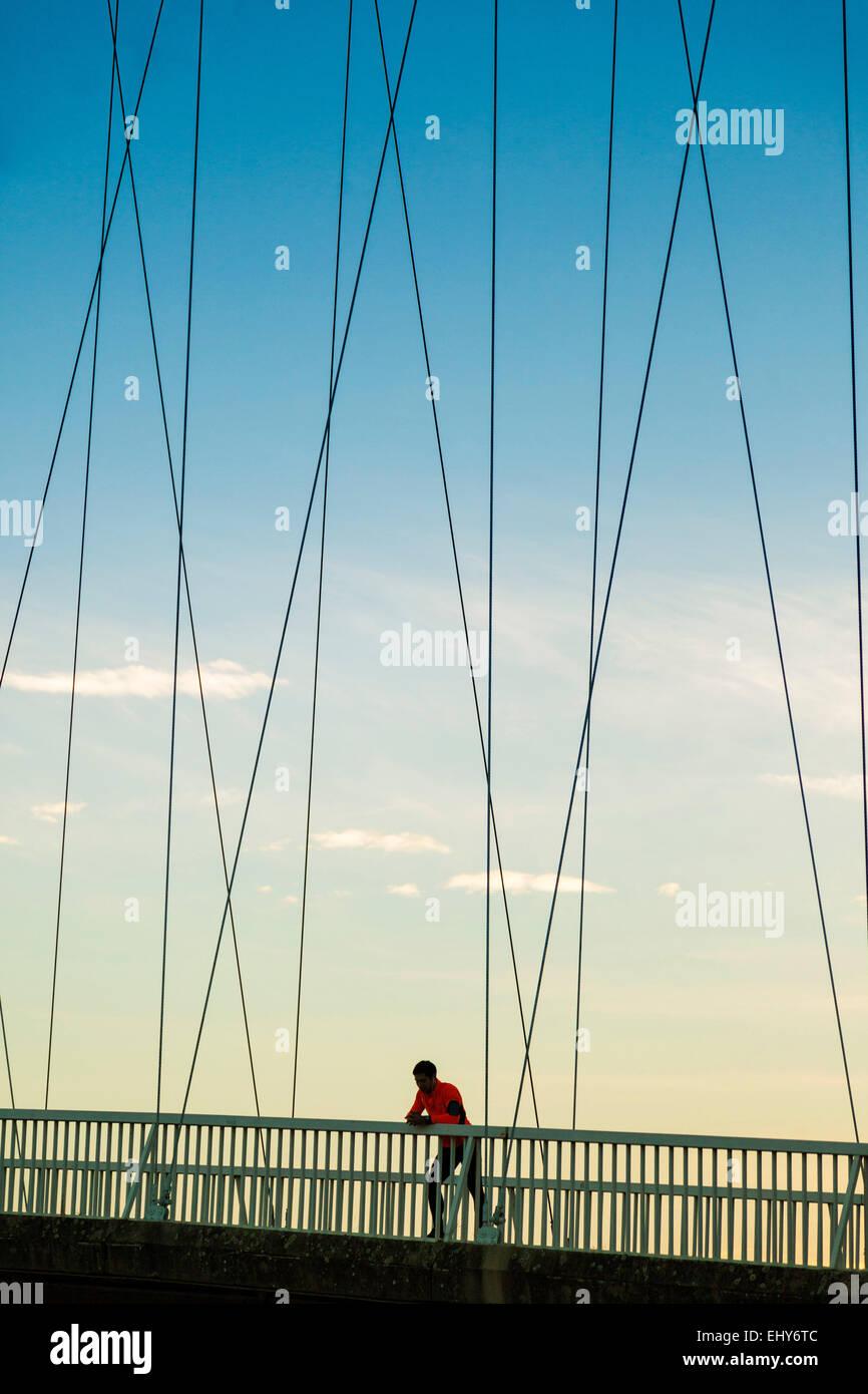 Männliche Läufer auf Brücke nimmt sich eine Auszeit Stockbild