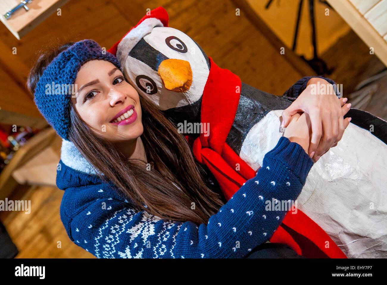 Junge Frau posiert mit Pinguin Figur Stockbild