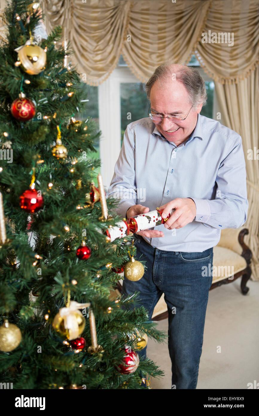 Senior woman Eröffnung Christmas Cracker Weihnachtsbaum Stockbild