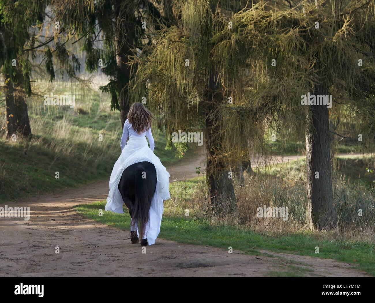 Rückansicht einer reifen Frau auf einem Pferd in einem weißen Kleid Stockbild