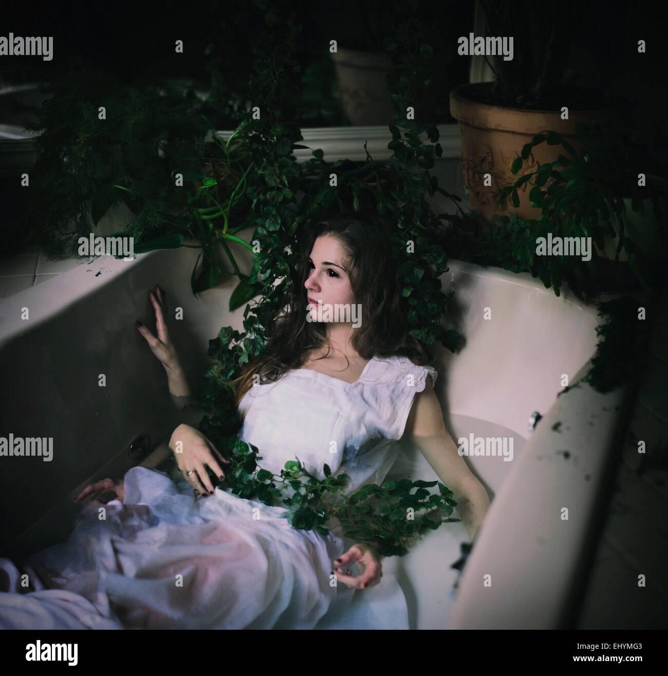 Junge Frau in einer Badewanne mit vielen Händen und Reben liegt Stockbild