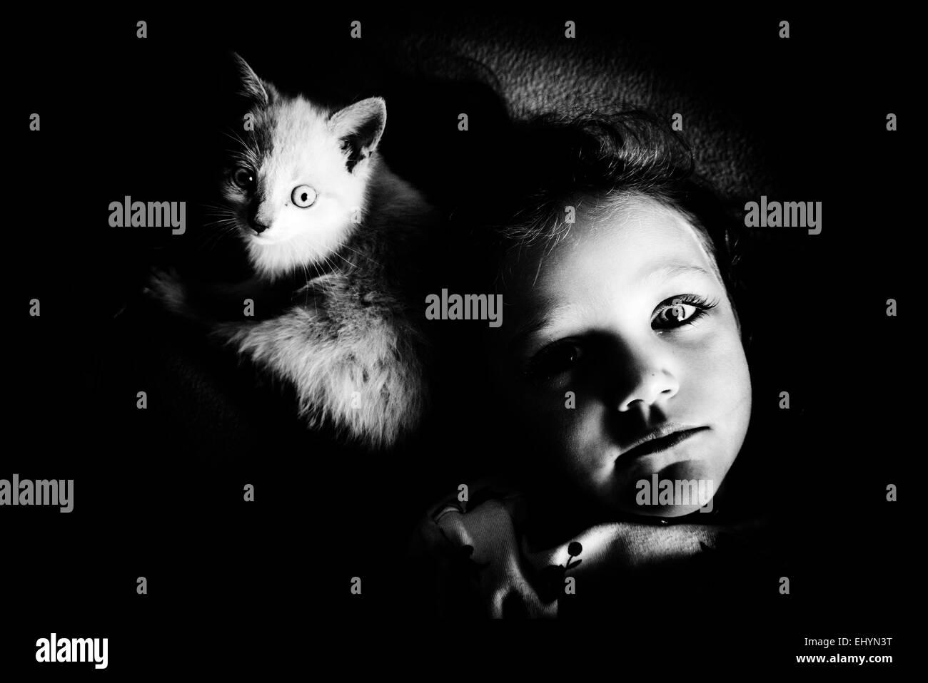 Mädchen liegend mit ihrer Katze Stockbild