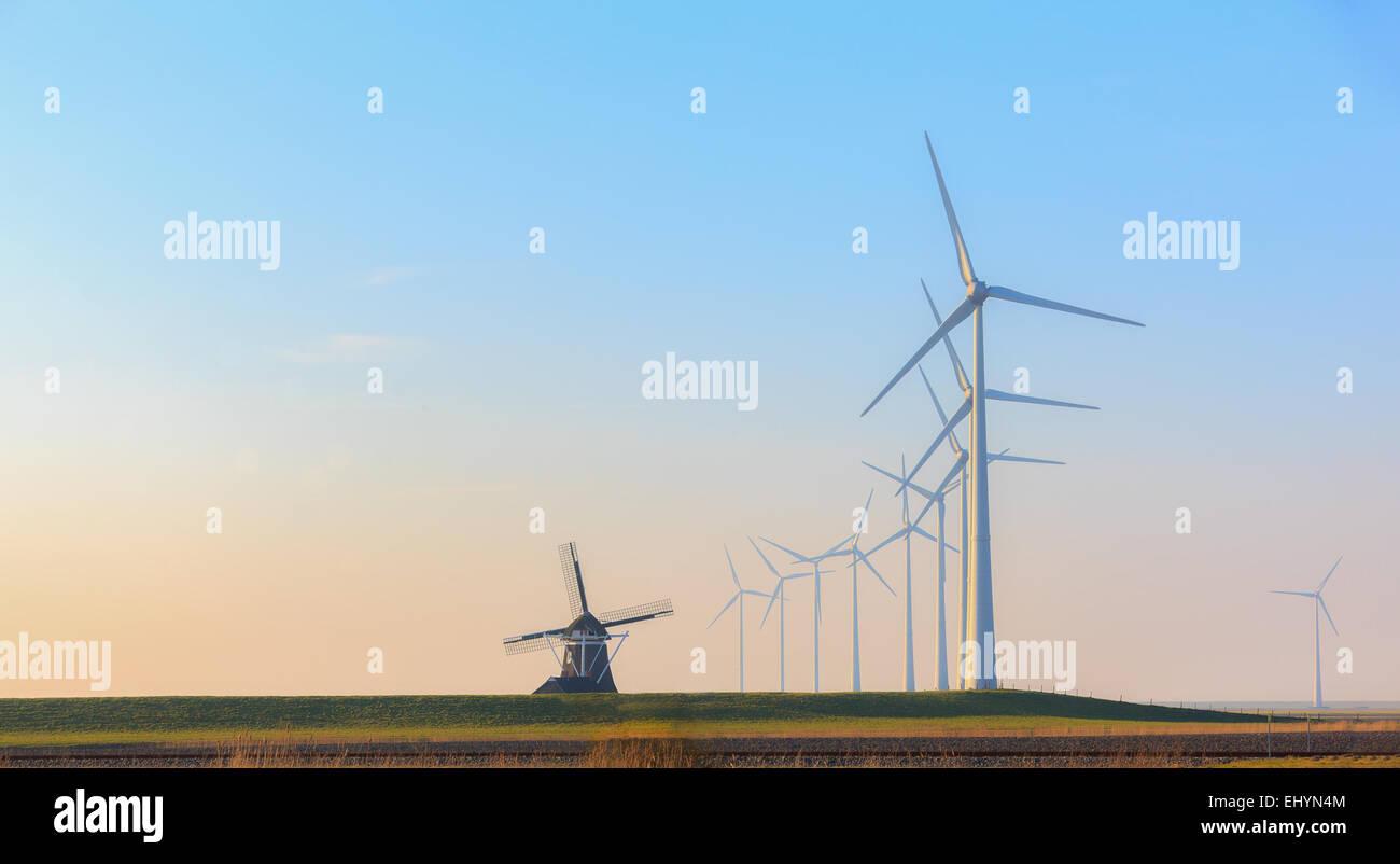 Reihen von Windenergieanlagen und einer alten traditionellen Windmühle, Eemshaven, Groningen, Niederlande Stockbild
