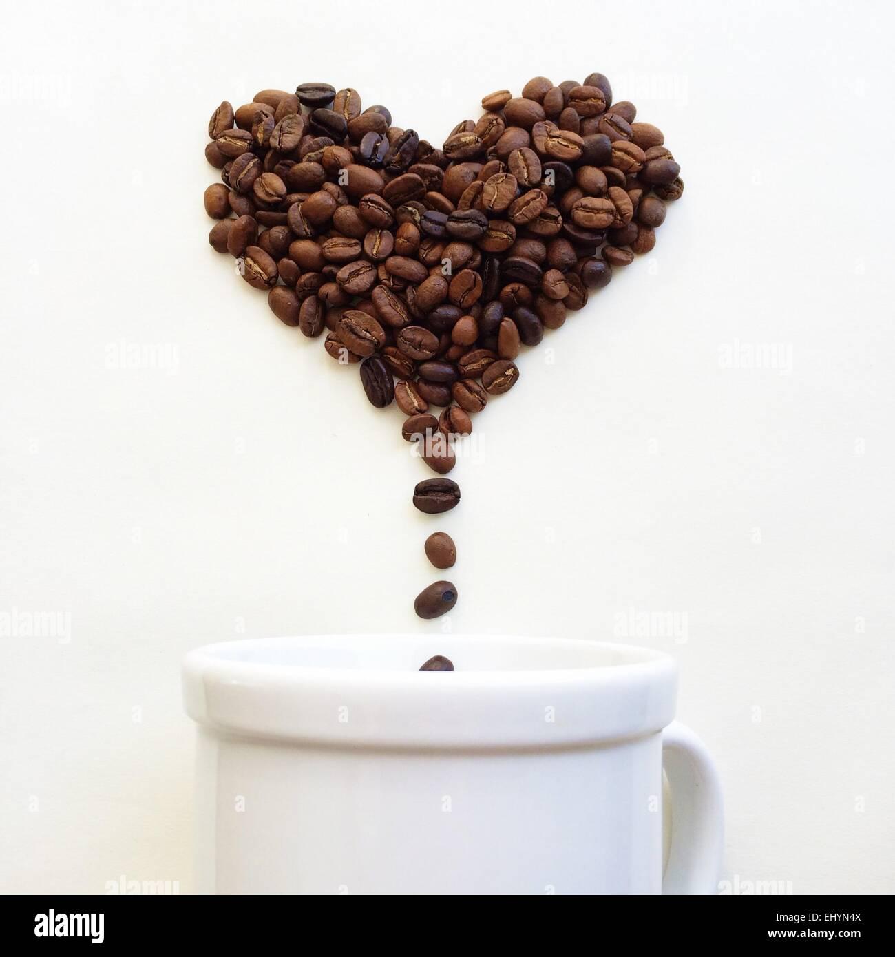 Kaffeebohnen in Form von Herzen fallen in eine Kaffeetasse Stockbild