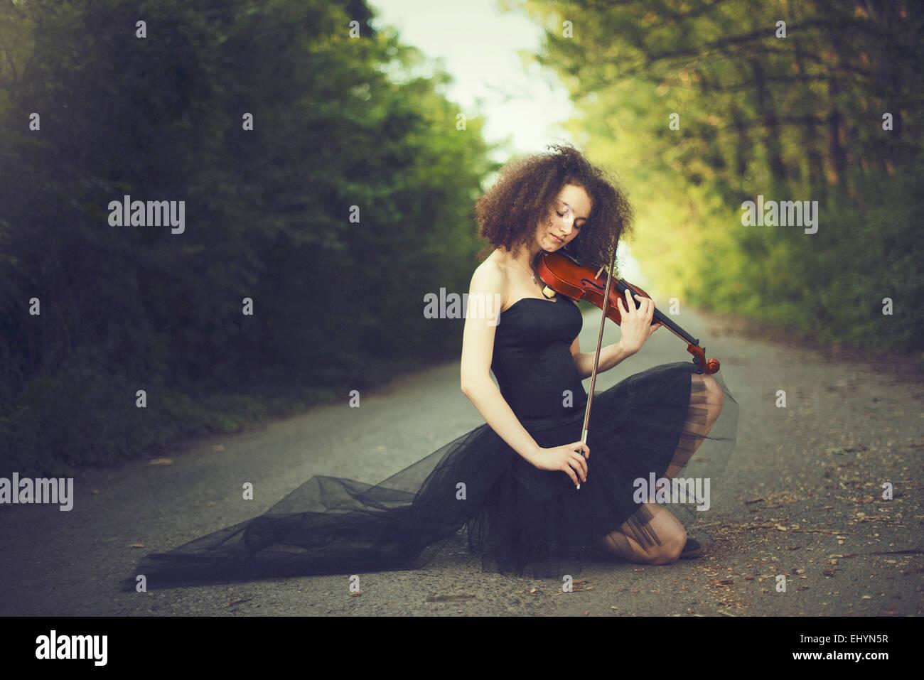Traurige junge Frau mit dem Geigenspiel Stockbild