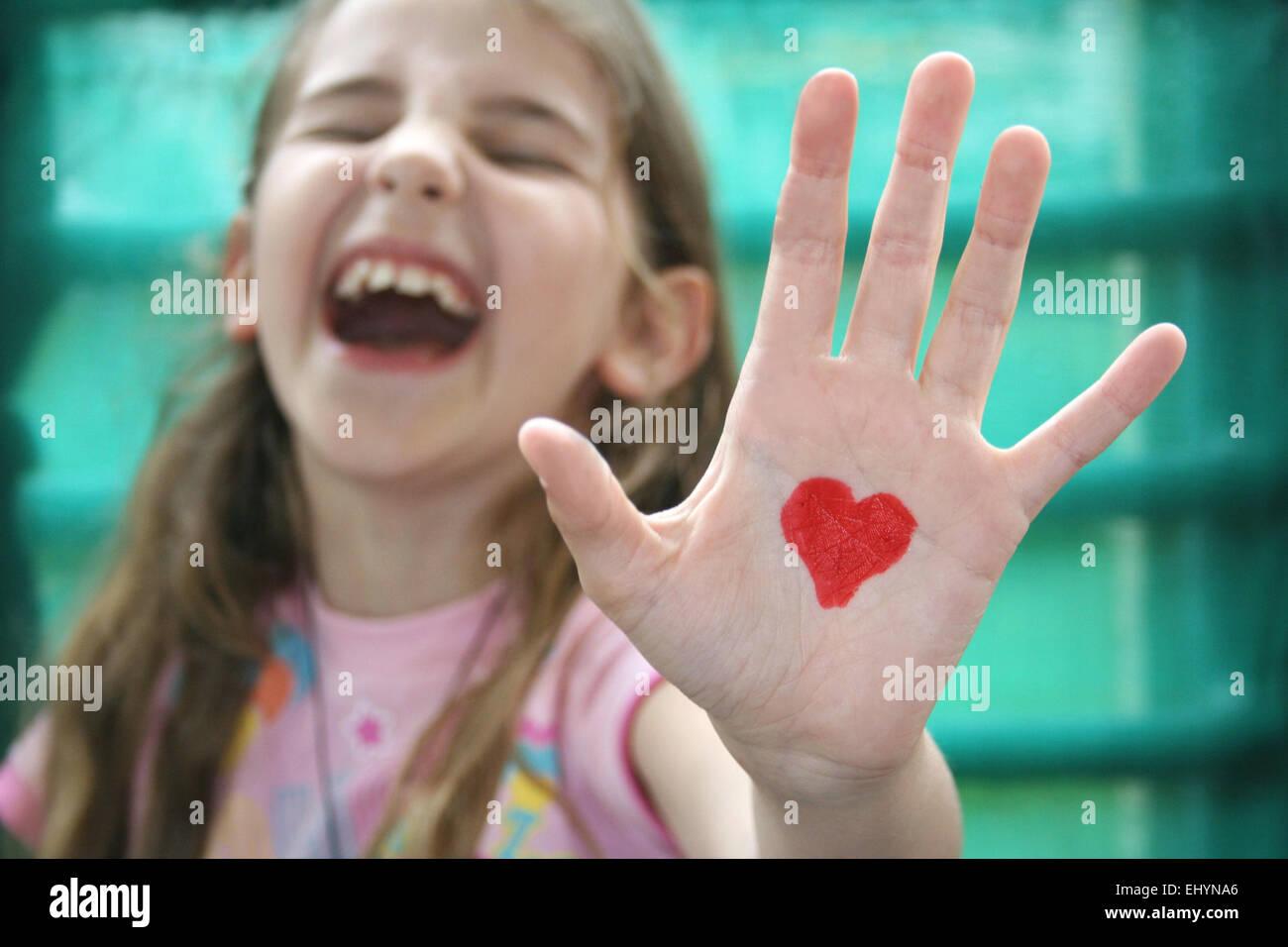 Mädchen mit einem Herzen auf der Handfläche von ihrer Hand gezeichnet Stockbild