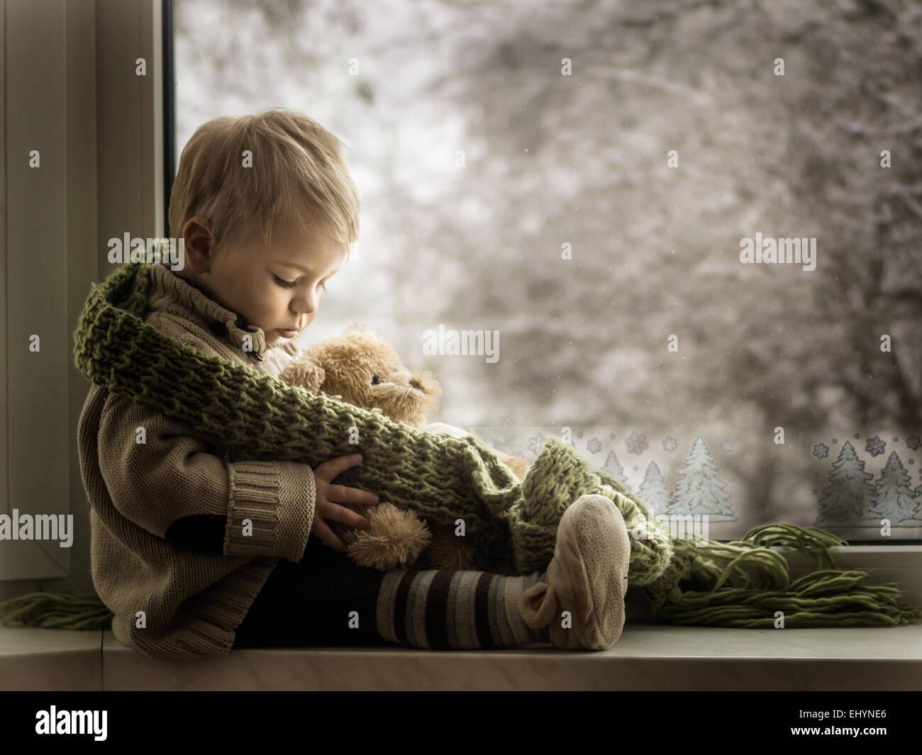 Junge sitzt auf einer Fensterbank mit einem Teddy-Bären Stockbild