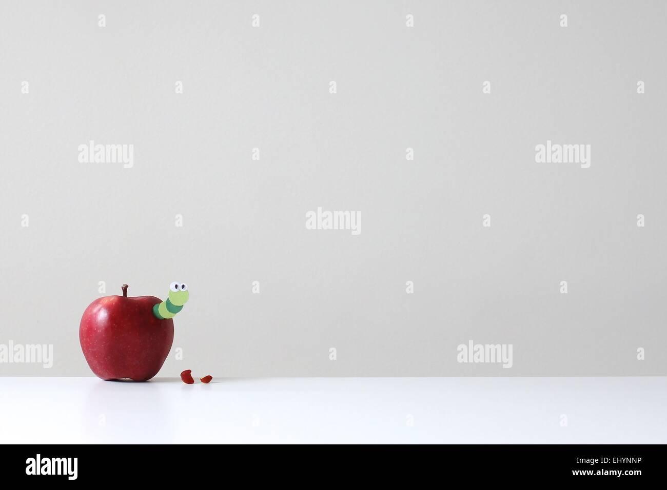 Ein roter Apfel mit einem Grünbuch Wurm stossen Stockbild