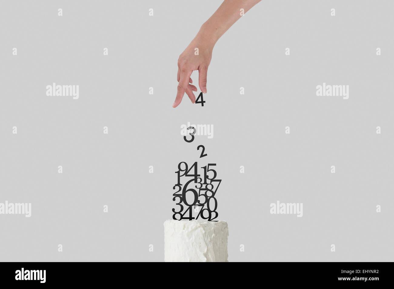 Eine Hand streuen einige Zahlen auf einer weißen Geburtstagstorte Stockbild