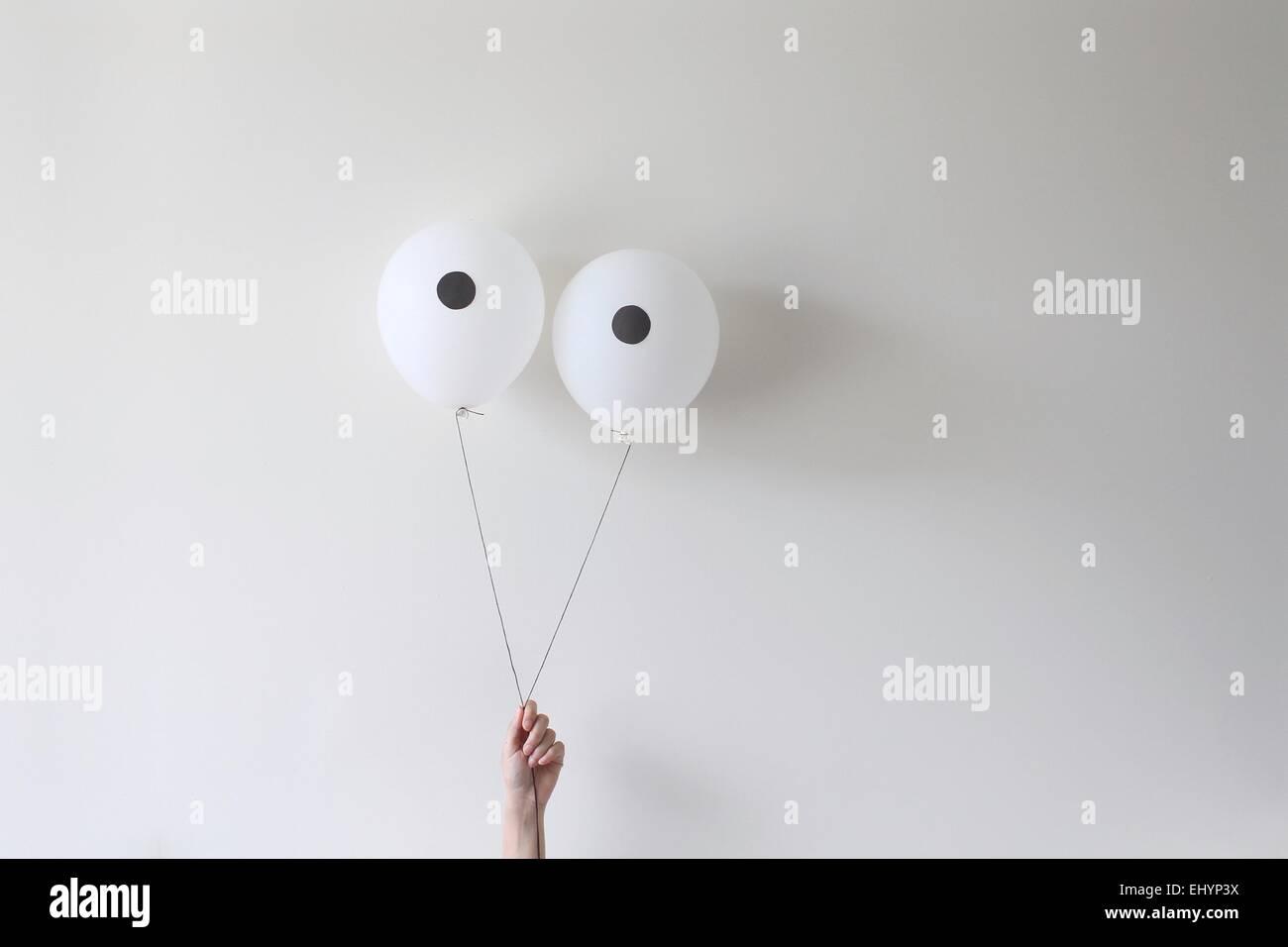 Eine Hand hält ein paar Ballons, die wie Augen Aussehen Stockbild