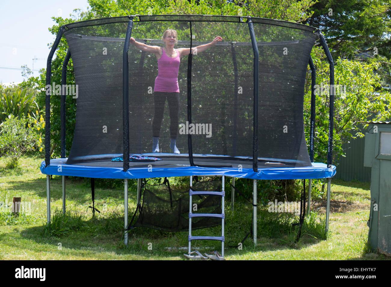 Ältere Frau hüpfen auf dem Trampolin im Garten Stockbild