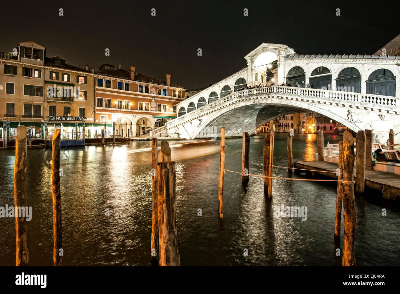 Pier mit Boot am Canal Grande bei der Rialto-Brücke in der Nacht. Stockfoto