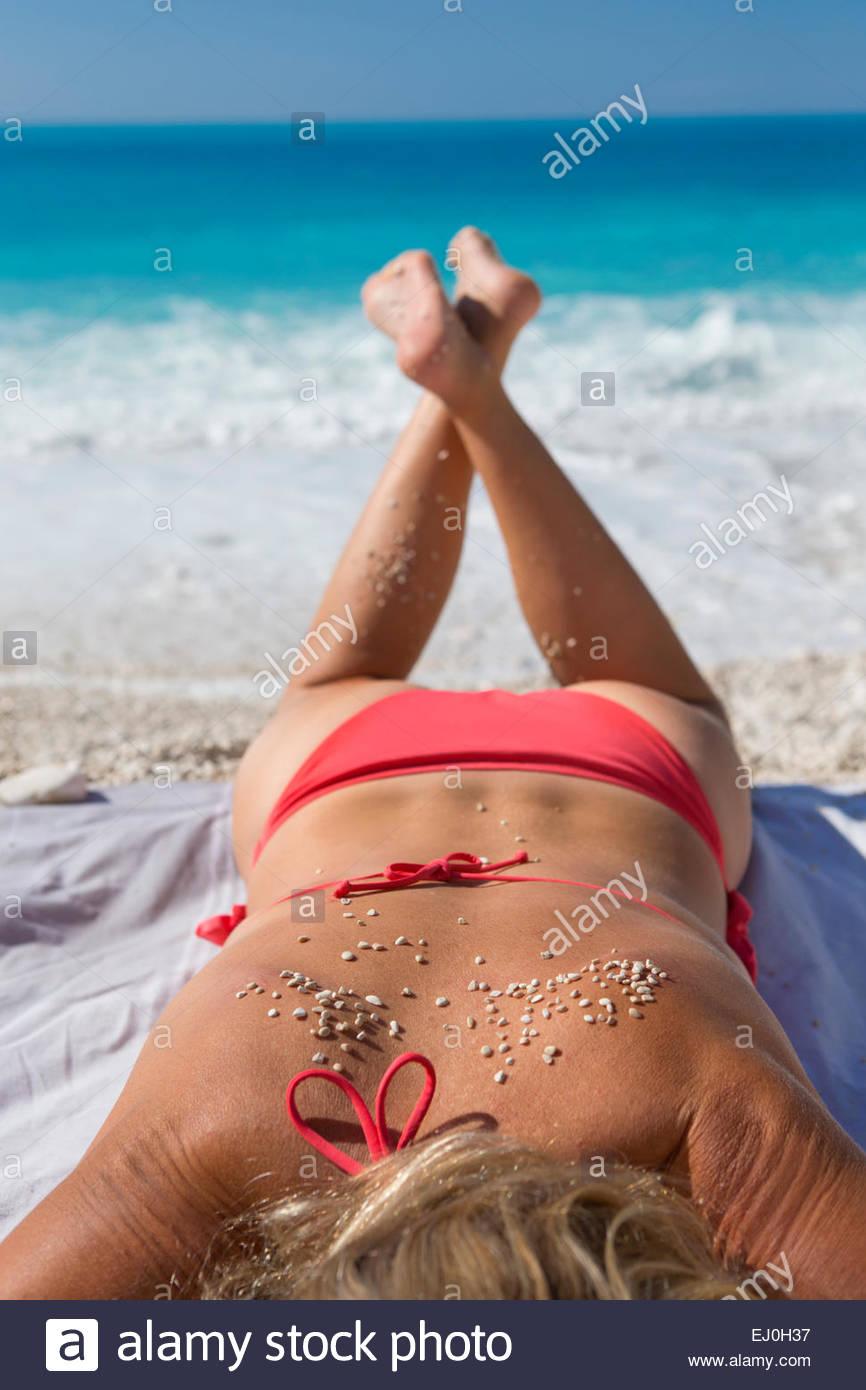 Frau, Sonnenbaden mit Sand am Rücken, am Sonnenstrand Stockbild