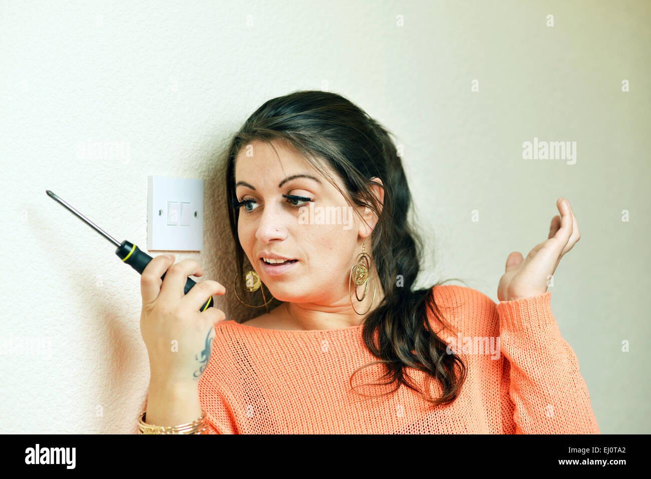 Frau verwirrt durch elektrische DIY zu Hause Stockbild