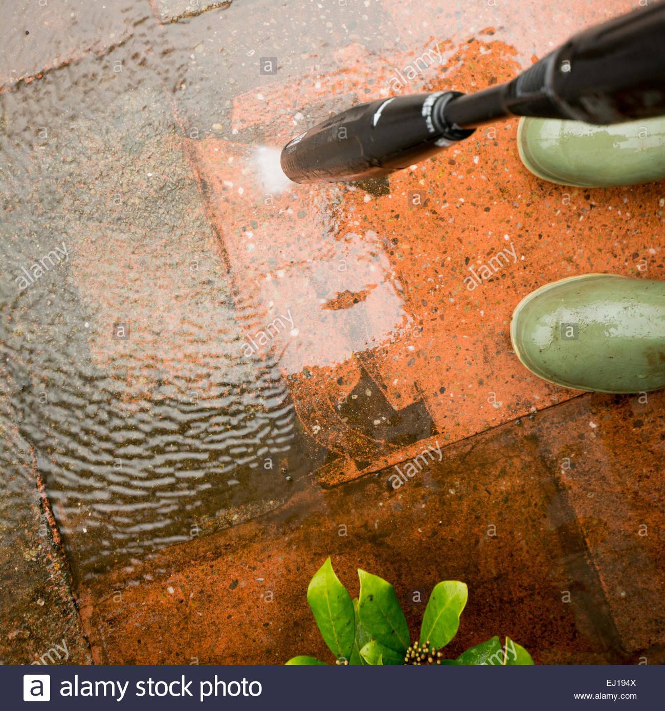 Macht waschen Terrasse - zeigt grüne Gummistiefel und macht Schlauch Stockbild