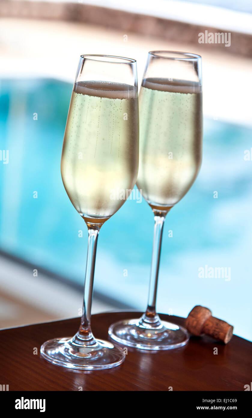 Champagner POOL LUXUS Zwei frisch Gläser Champagner und Kork auf Alfresco Terrasse Tisch mit luxuriösen Infinity Stockfoto