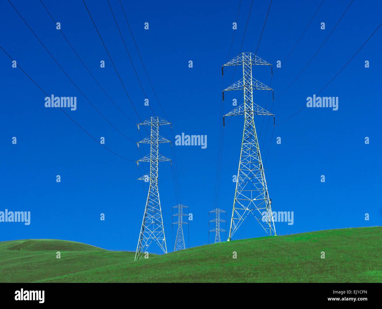 Strommasten stehen auf hügeligen grünen Rasen mit tiefblauen Himmel Stockbild