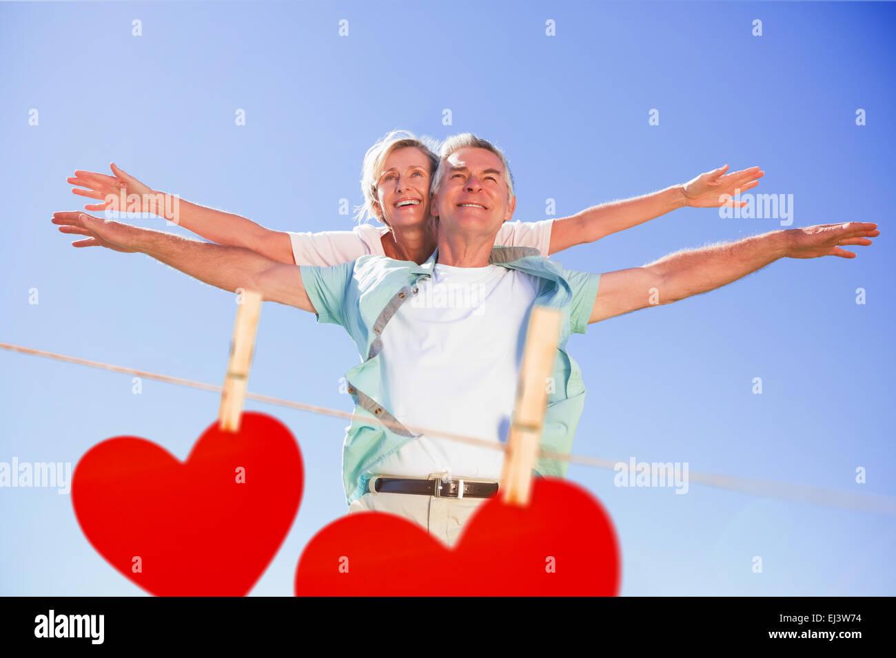 Zusammengesetztes Bild der senior glücklich mit seiner Partnerin eine Huckepack Stockbild