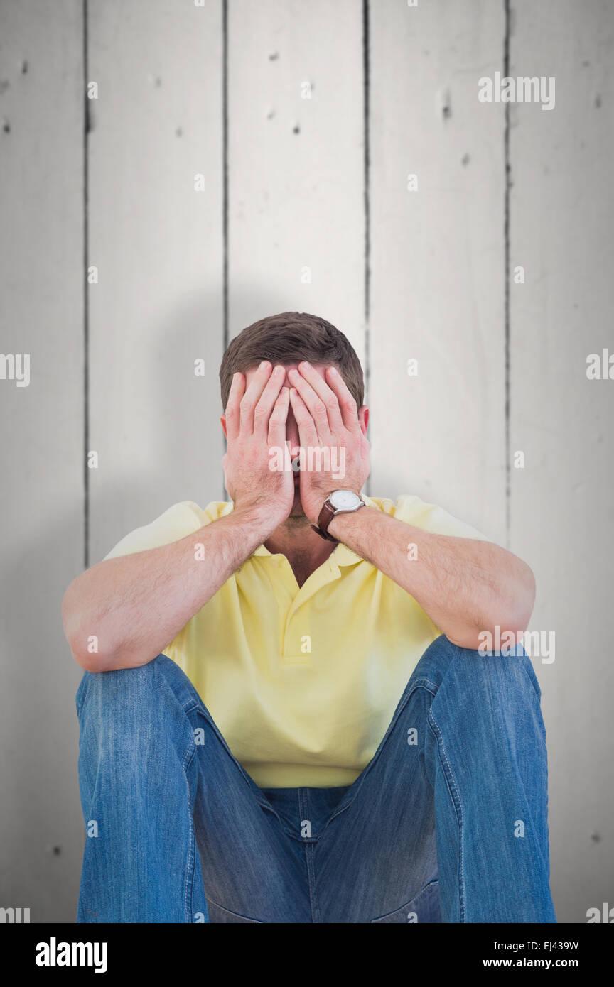 Zusammengesetztes Bild von legerer Mann mit Kopf in Händen Stockbild