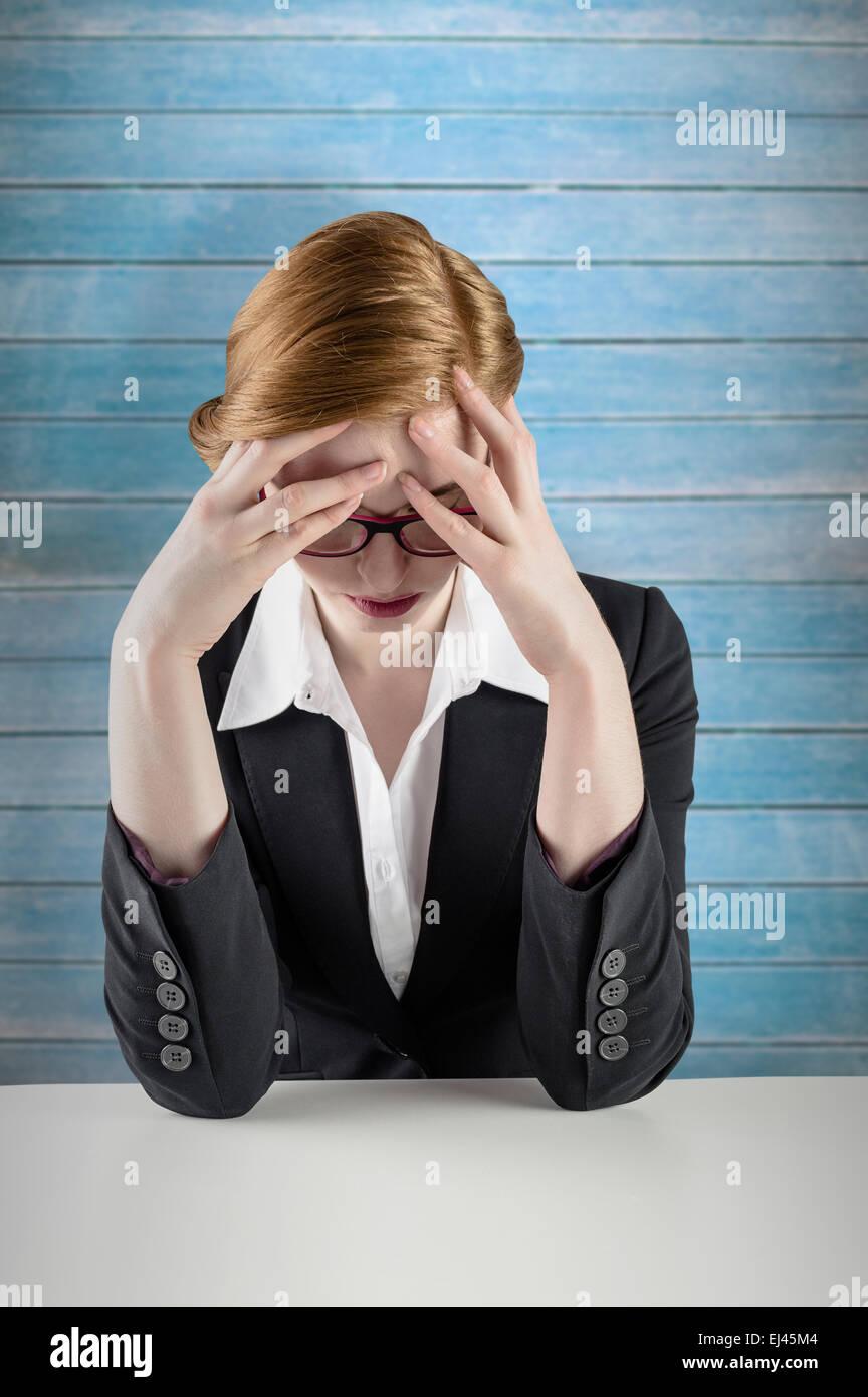 Zusammengesetztes Bild der rothaarige Geschäftsfrau mit Kopf in Händen Stockbild