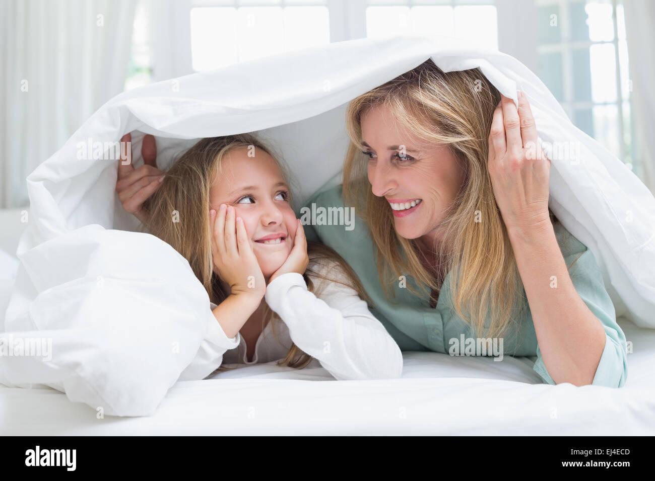 Mutter und Tochter sahen einander unter der Bettdecke Stockbild