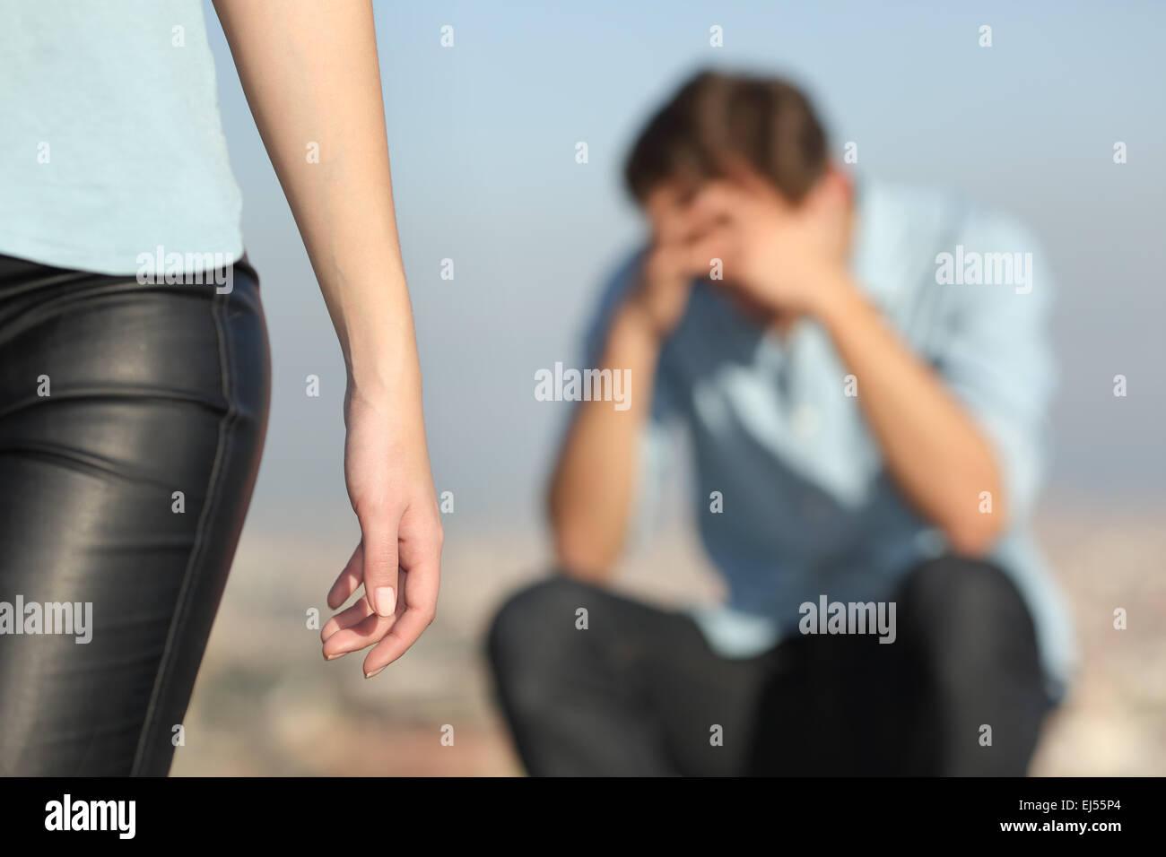 Trennung eines Paares mit einem traurigen Mann im Hintergrund und die Freundin ließ ihn in den Vordergrund Stockbild