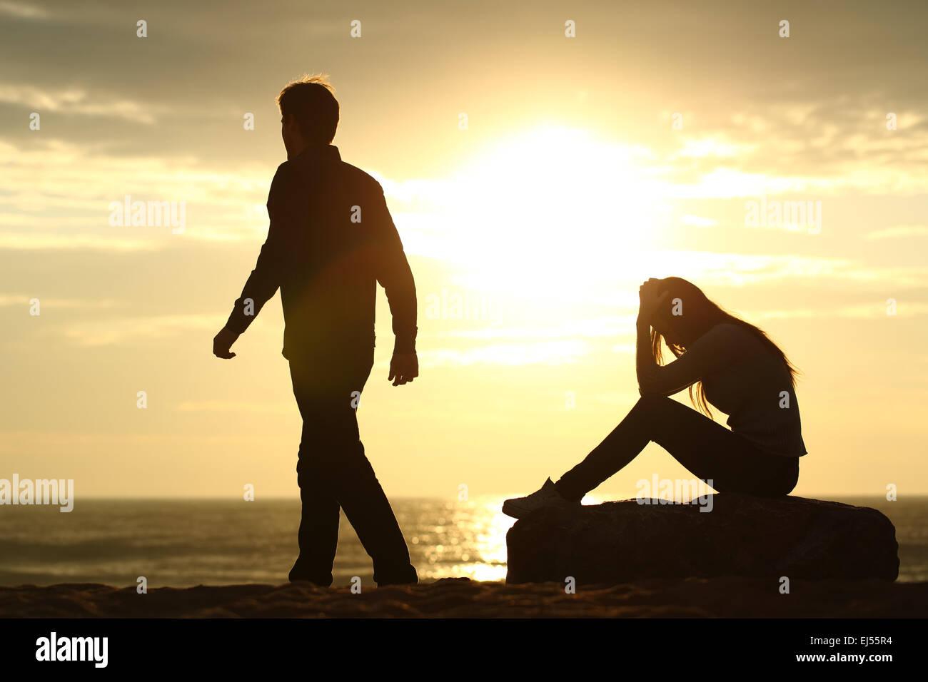 Paar Silhouette aufbrechen einer Beziehung am Strand bei Sonnenuntergang Stockbild
