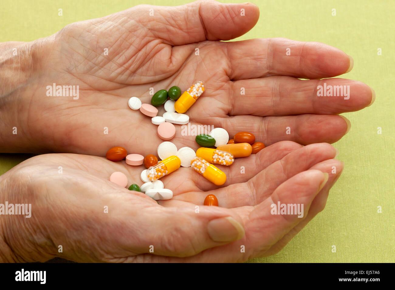 Hohlen Hand einer alten Dame mit einem Cocktail aus Tabletten Kapseln und Pillen, die ihr als Medikation und Behandlung Stockbild