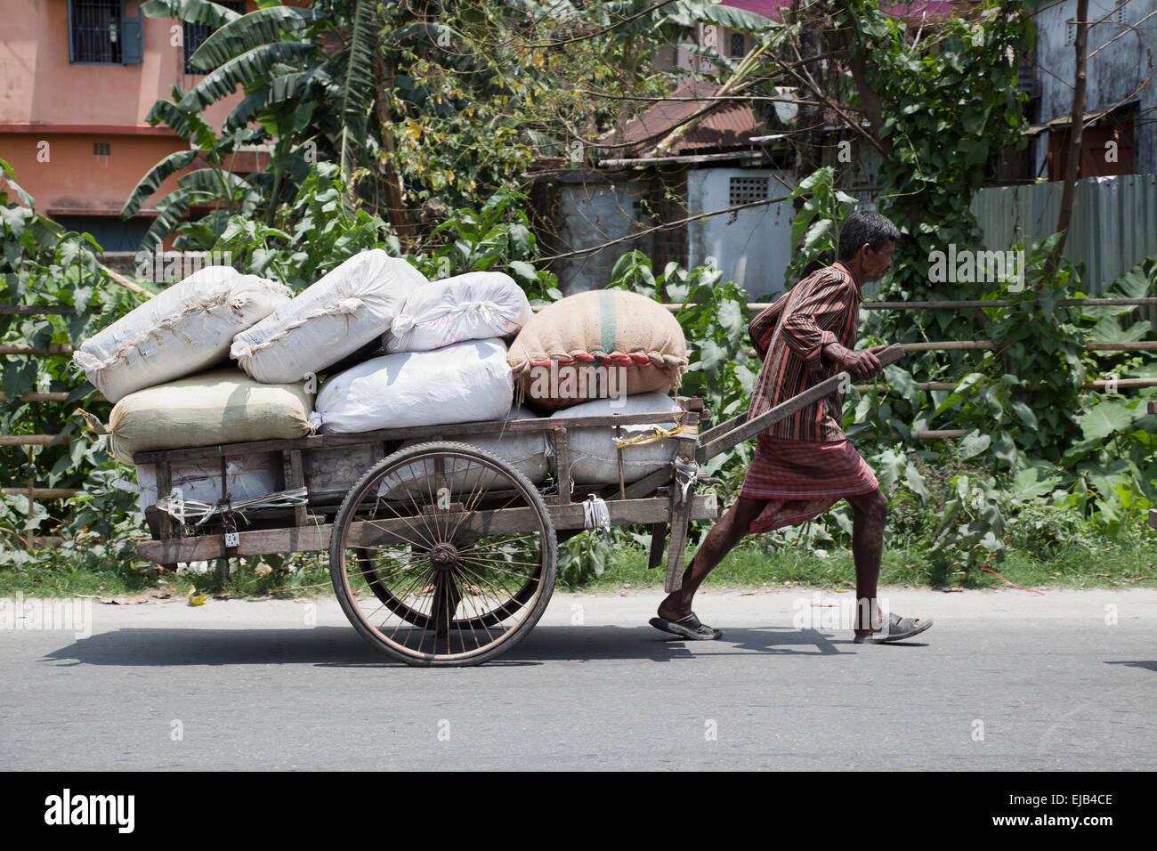 Arbeiter kämpfen mit schweren Last Cooch Behar, Westbengalen, Indien Stockbild