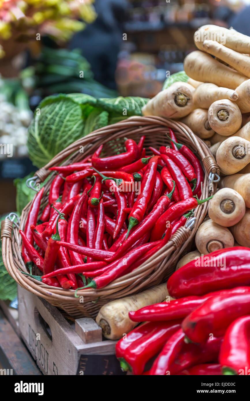 Ein Korb mit roten Chilischoten angezeigt auf einem Gemüse stand vor dem Hintergrund der Pastinaken und Kohl Stockbild