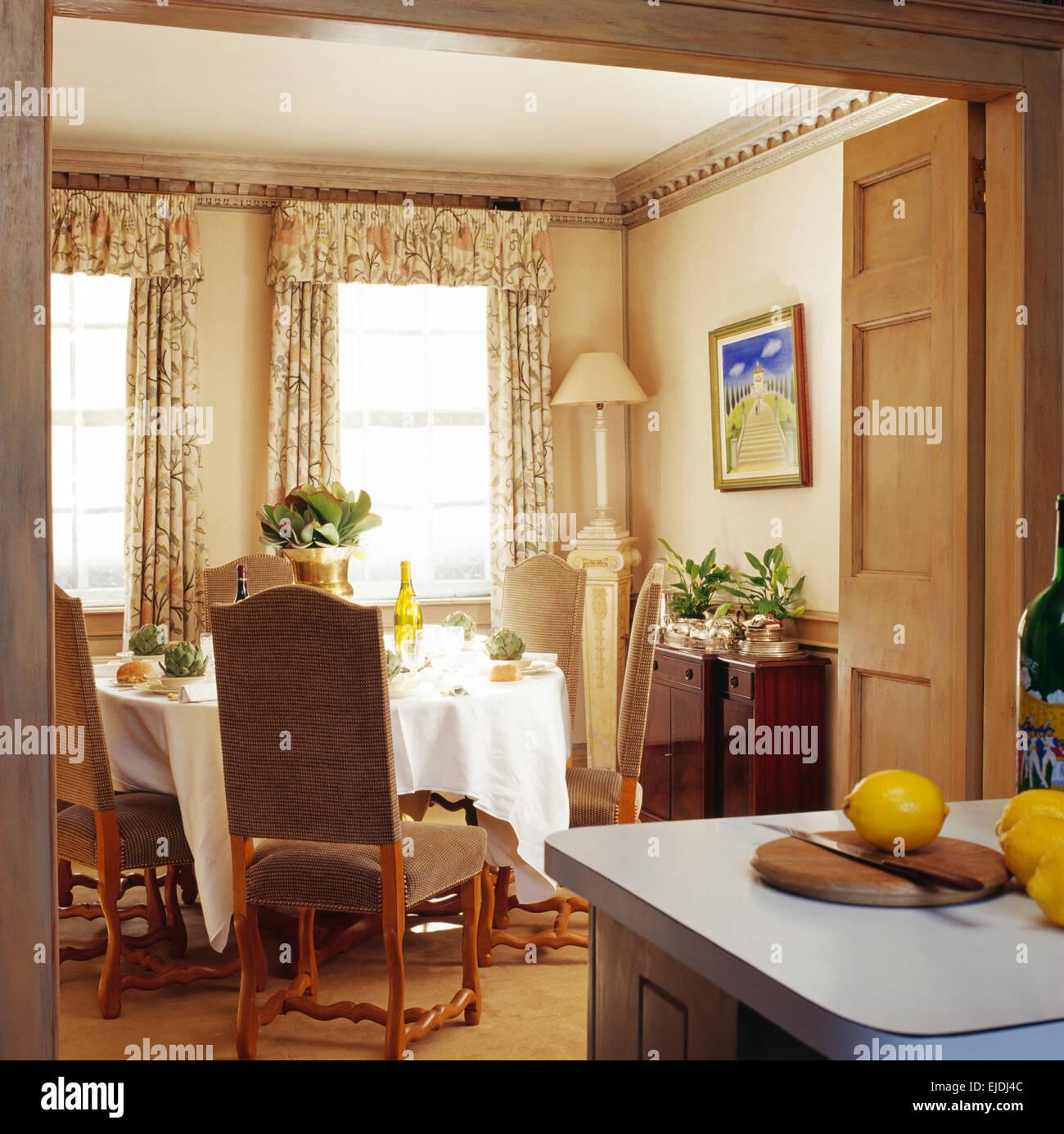 Dunkelbeige gepolsterte Stühle am Esstisch mit weißen Leinentuch im ...