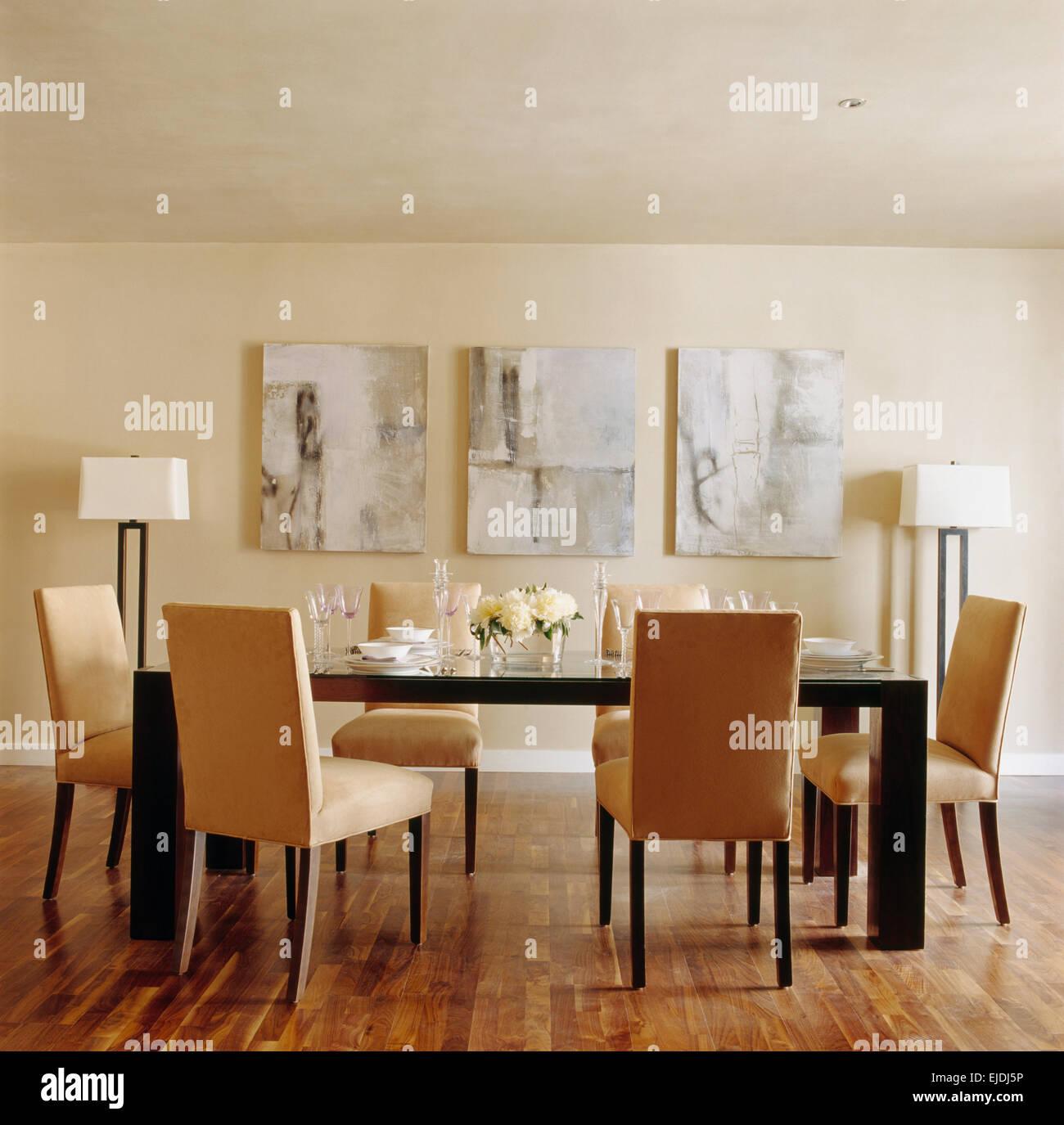Wildleder gepolsterte Stühle und Glas gekrönt schwarzen Tisch im modernen Speisesaal mit abstrakten Gemälde Stockbild