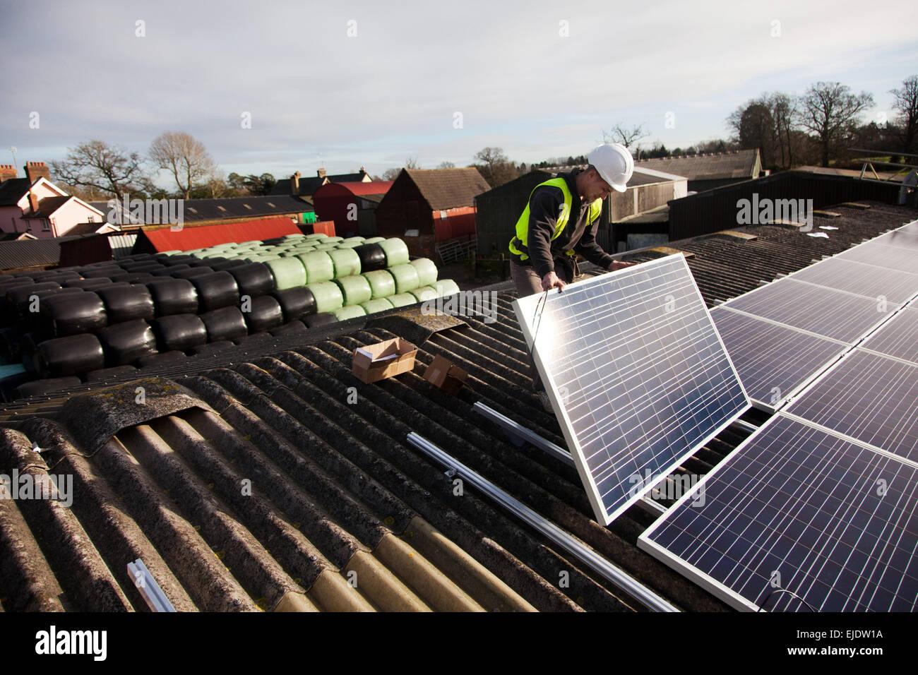 Jake Beautyman installiert Solarzellen auf dem Dach der Scheune auf Grange Farm nahe Balcombe. Die Installation Stockbild