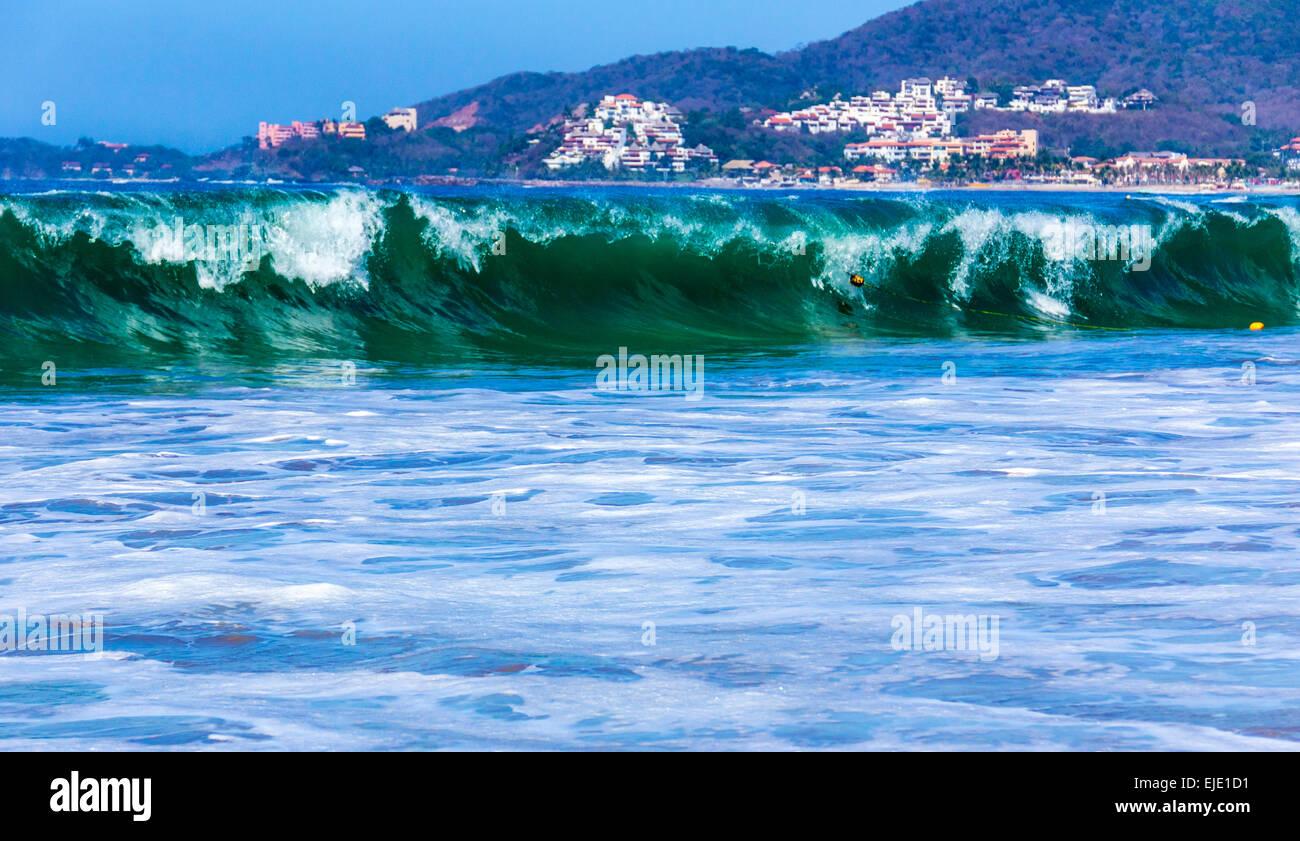 Wellen von Ixtapa/Zihuatanejo Bay Resorts im Hintergrund. Stockbild