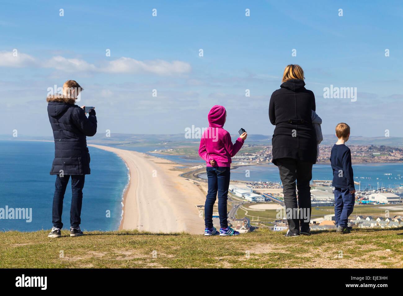 Eine deutsche Familie sind fotografieren und genießen den Blick auf Portland Harbour und Chesil Beach an einem sonnigen Stockfoto