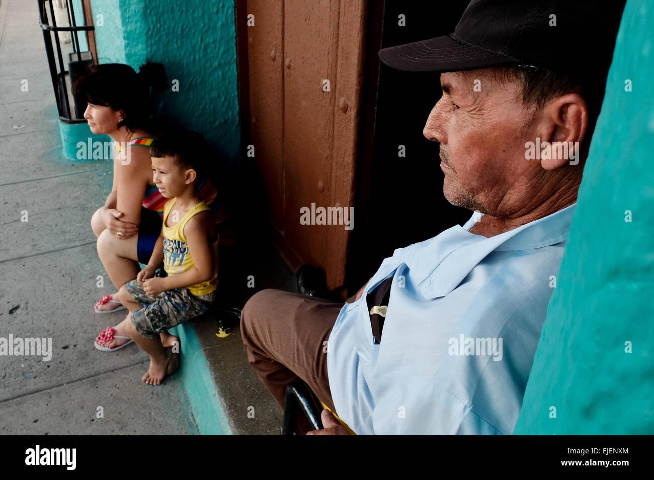 Ein Mann wacht über seine Familie vor der Haustür zu ihrem Haus in der 500 Jahre alten Stadt Sancti Spíritus, Stockbild