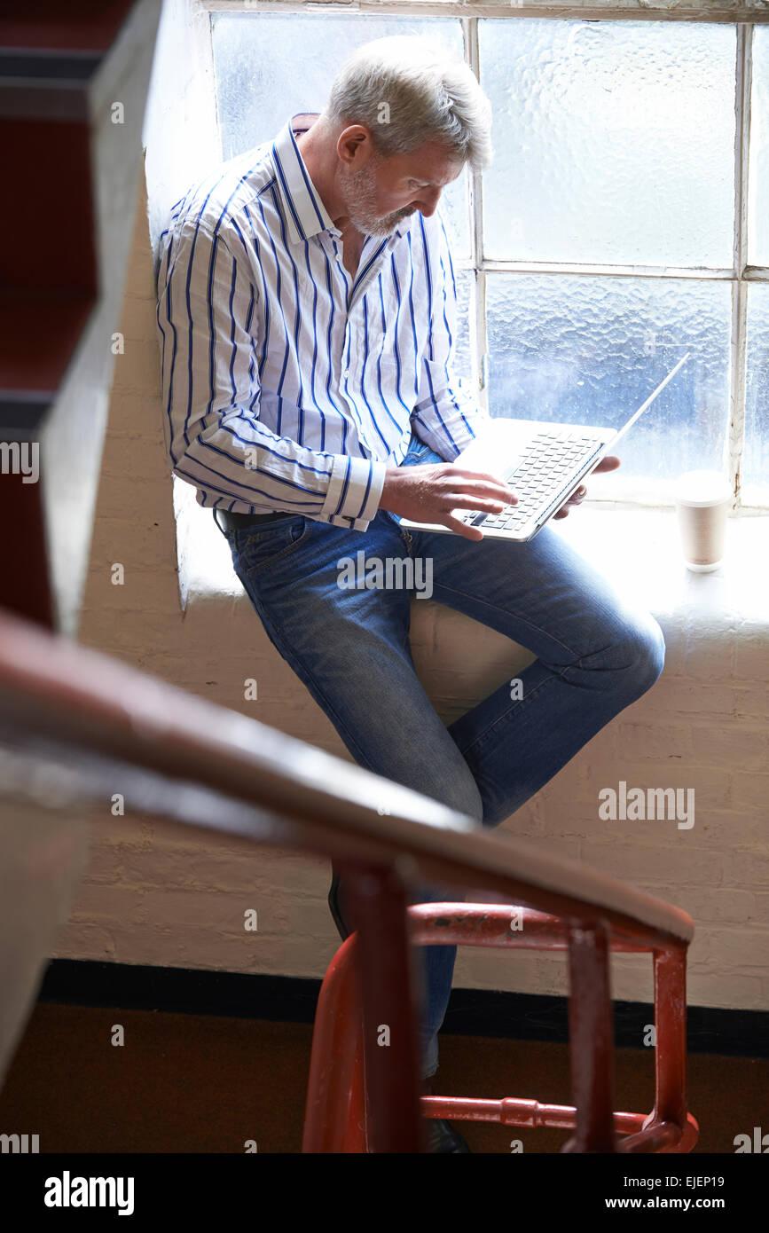 Leger gekleidet Geschäftsmann arbeiten auf Treppen im Büro Stockbild
