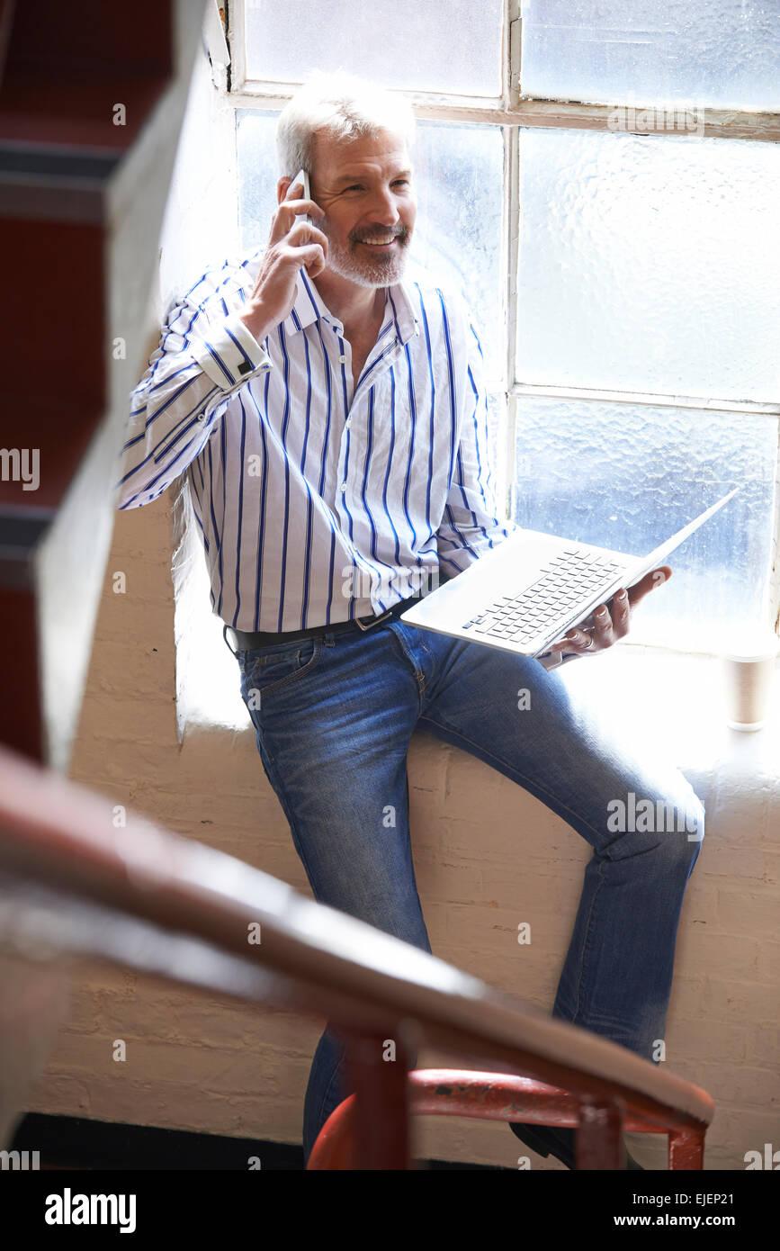 Leger gekleidet Geschäftsmann arbeiten auf Treppen im Büro telefonieren mit Handy Stockbild