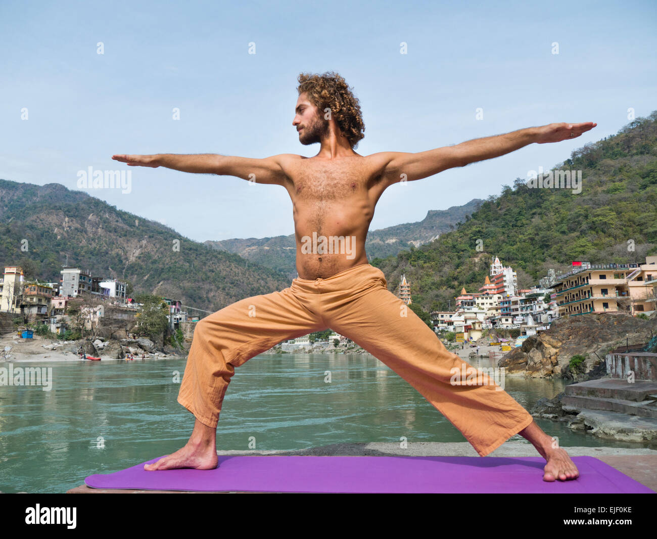 Ein Mann üben Yoga-Krieger-Pose am Ganges-Fluss in Rishikesh, Indien Stockbild